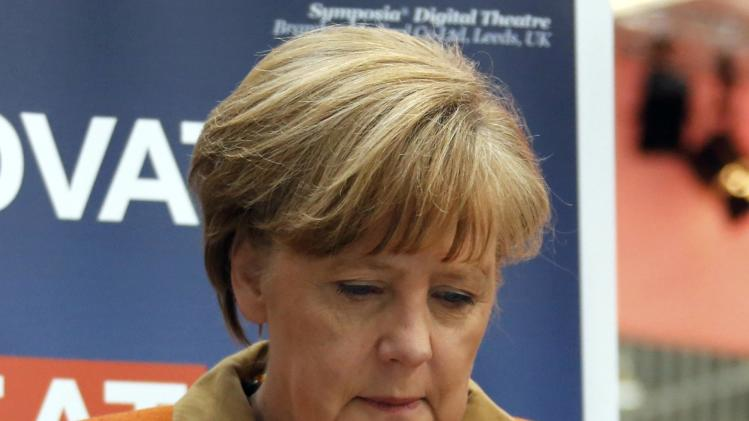 German Chancellor Merkel looks at a bionic hand during a tour at the CeBIT technology fair in Hanover