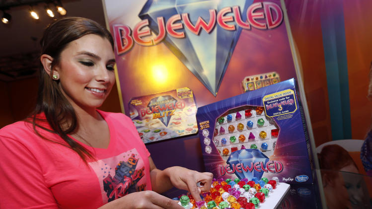 IMAGE DISTRIBUTED FOR HASBRO - Game demonstrator Aubree Marchione matches colored gems in Hasbro's new BEJEWELED Game in the company's showroom at the American International Toy Fair, Monday, Feb. 11, 2013, in New York. (Photo by Jason DeCrow/Invision for Hasbro/AP Images)