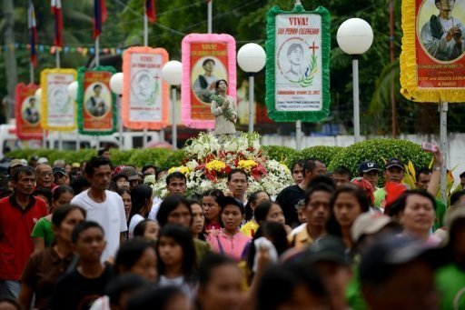Philippine Catholics carry a statue of Pedro Calungsod -- the new patron saint for the youth