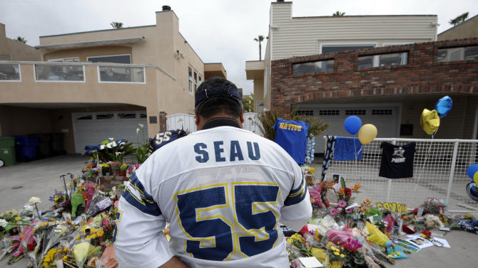 """San Diego Chargers fan Jerry Lopez looks over a memorial set-up in the driveway of the house of former NFL star Junior Seau Thursday, May 3, 2012, in Oceanside, Calif. Seau's apparent suicide stunned an entire city and saddened former teammates who recalled the former NFL star's ferocious tackles and habit of calling everybody around him """"Buddy.""""  (AP Photo/Denis Poroy)"""