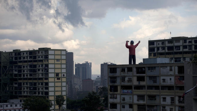 A giant inflatable doll representing President Hugo Chavez stands on top of a building in Caracas, Venezuela, Saturday, Oct. 6, 2012. Chavez is running for re-election against opposition leader Henrique Capriles in Sunday's presidential election. (AP Photo/Ramon Espinosa)