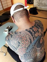 A retired Japanese yakuza crime boss shows the tattoo on his back featuring a carp swimming up a waterfall, at his home in Tokyo on March 20, 2009