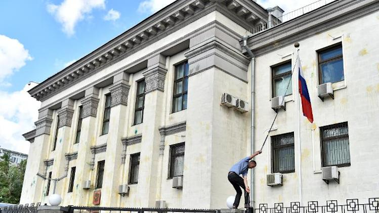 A man takes down the Russian flag during a protest at the embassy in Kiev on June 14, 2014