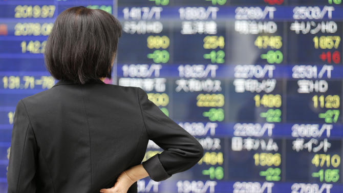 A woman watches an electronic stock board of a securities firm in Tokyo, Thursday, May 16, 2013. Asian stock markets were mixed Thursday following dour European economic data that dampened hopes of a recovery there anytime soon. However, losses were limited by another record session on Wall Street. (AP Photo/Koji Sasahara)