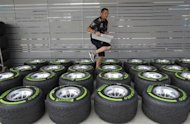 A team member walks amid Pirelli tyres outside the Red Bull garage at the Buddh International Circuit in Greater Noida on the outskirts of New Delhi October 24, 2013. REUTERS/Anindito Mukherjee