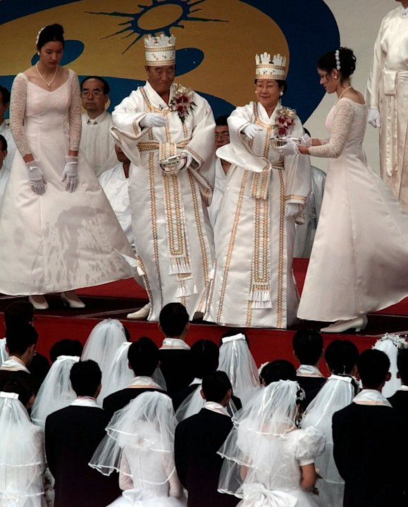 FILE - In this Saturday, Nov. 29, 1997 file photo, the Rev. Sun Myung Moon, center left, and his wife Hak Ja Han Moon officiate a mass wedding ceremony during at RFK Stadium in Washington. Moon, self-