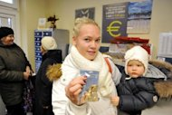 Linda Grabouska shows an euro starter pack, containing a mixture of euro coins, she picked up with her daughter Jasmina at the Marupe post office near the Riga airport, on December 10, 2013