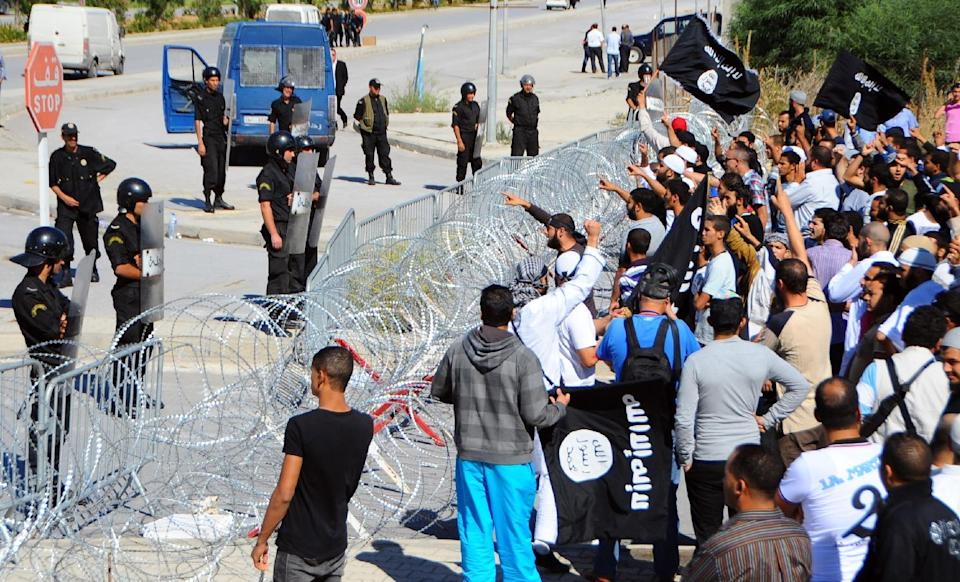 Protestors, right, face-off against riot police officers guarding the US embassy in Tunis, Friday, Sept. 14, 2012.  Angry demonstrations against a perceived anti-Islamic film spread around the Middle East Friday. (AP Photo/Hassene Dridi)
