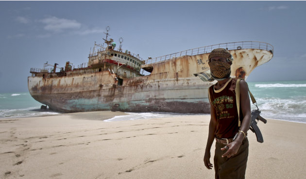 In this photo taken Sunday, Sept. 23, 2012, masked Somali pirate Abdi Ali stands near a Taiwanese fishing vessel that washed up on shore after the pirates were paid a ransom and released the crew, in