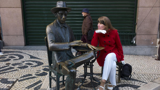 In this photo taken Jan. 1 2013, a tourist poses for a snapshot next to the statue of Portuguese poet Fernando Pessoa in Lisbon's Chiado neighborhood. The Chiado's heyday was in the late 19th-century Belle Epoque when writers and artists gathered at its cafes. Outside the Cafe A Brasileira, the statue of Fernando Pessoa, Portugal's best-known 20th-century poet who also wrote in English, is one of the city's most-photographed sights. (AP Photo/Armando Franca)