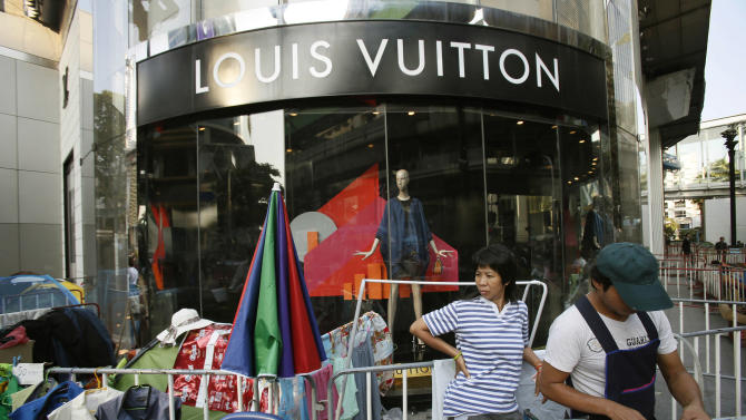 A luxury fashion shop is surrounded by anti-government protesters in central Bangkok, Thailand, Wednesday, Jan. 29, 2014. The latest spasm in Thailand's ongoing political upheaval is taking an economic toll as anti-government protesters barricade Bangkok's major intersections and confrontations between protesters and government supporters periodically flare into deadly clashes. (AP Photo/Wally Santana)
