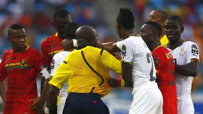 Assistant referee Evarist Menkouande tries to break up Ghana and Guinea players during their quarter-final soccer match of the 2015 African Cup of Nations in Malabo
