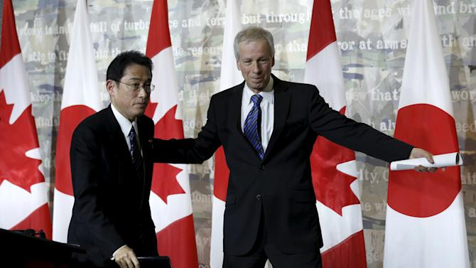 Canada's Foreign Minister Dion and his Japanese counterpart Fumio Kishida leave at the conclusion of a news conference in Ottawa