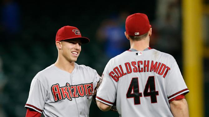 Arizona Diamondbacks' Jake Lamb, left, congratulates Paul Goldschmidt after the 4-3 win over the Seattle Mariners in ten innings of a baseball game on Monday, July 27, 2015, in Seattle. (AP Photo/John Froschauer)