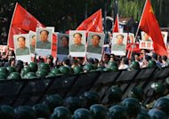Demonstrators march holding images of former Chinese leader Mao Zedong (C) as police stand guard outside the Japanese embassy in Beijing as anti-Japanese protests continue across the country over the Diaoyu islands issue, known as the Senkaku islands in Japanese, on September 18, 2012