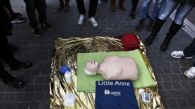 "People stand around mannequin ""Little Anne"" during CPR course in Athens"
