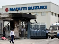 Indian private security guards stand behind the main gate of Maruti Suzuki Production Facility in Manesar, about 45 kms from New Delhi on July 19. India&#39;s biggest carmaker Maruti Suzuki reported a 23 percent plunge in quarterly profit, missing market forecasts as the company struggles to recover from deadly labour unrest