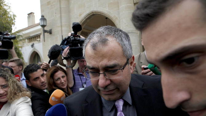Cyprus' Central Bank chief Panicos Demetriades surrounded by the media, leaves after the meeting outside the presidential palace in capital Nicosia, Thursday March 21, 2013. The European Central Bank says it will keep emergency aid for Cyprus' troubled banks in place at least until Monday but will have to cut it off after that unless an international rescue program is drawn up. (AP Photo/Petros Karadjias)