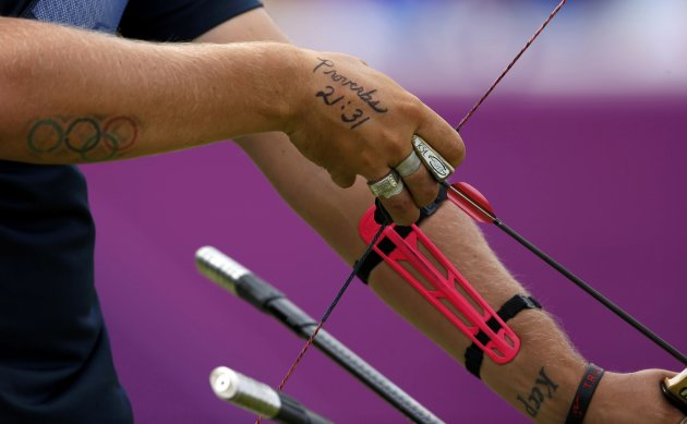 A tattoo of a Bible verse is seen on the hands of Brady Ellison of the U.S. as he prepares to take aim during the men's archery team quaterfinals at the Lords Cricket Ground during the London 2012