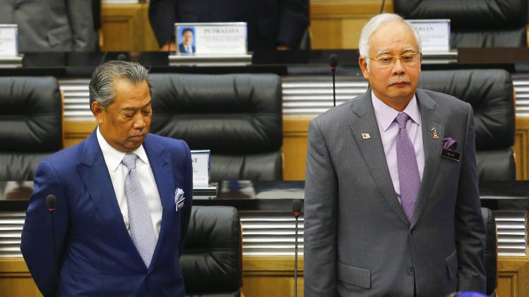 Malaysia's PM Najib Razak and Deputy PM Muhyiddin Yassin observe a moment of silence before the start of a special parliament session convened to discuss the MH17 tragedy at Parliament house in Kuala Lumpur