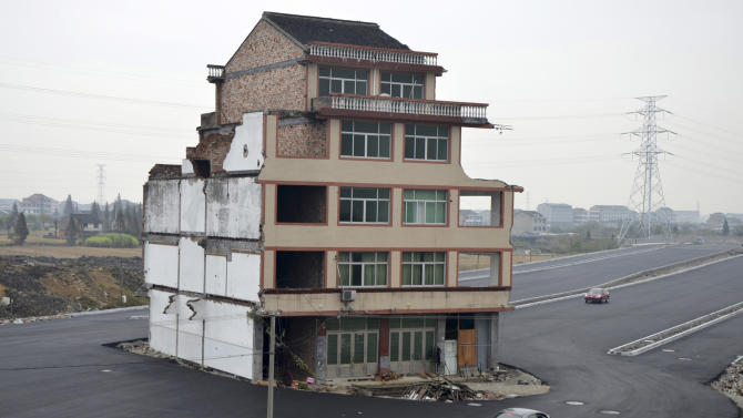 A car stops beside a house in the middle of a newly built road in Wenling
