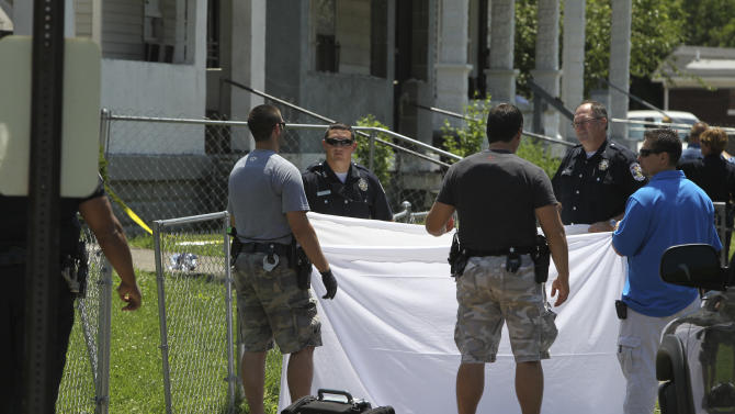 Investigators inspect the scene where four people were shot on a street corner in a west Louisville neighborhood Thursday, May 17, 2012. Police say two of the four people have died after being shot near 32nd and Kentucky Streets, and more gunfire rang out while officers were investigating. (AP Photo/The Courier-Journal, Michael Clevenger) NO SALES; MAGS OUT; NO ARCHIVE; MANDATORY CREDIT