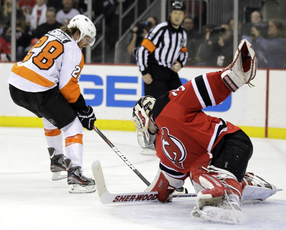 Philadelphia Flyers' Claude Giroux, left, scores on New Jersey Devils goalie Martin Brodeur during the first period of Game 4 of a second-round NHL hockey Stanley Cup playoff series, Sunday, May 6, 2012, in Newark, N.J. (AP Photo/Julio Cortez)