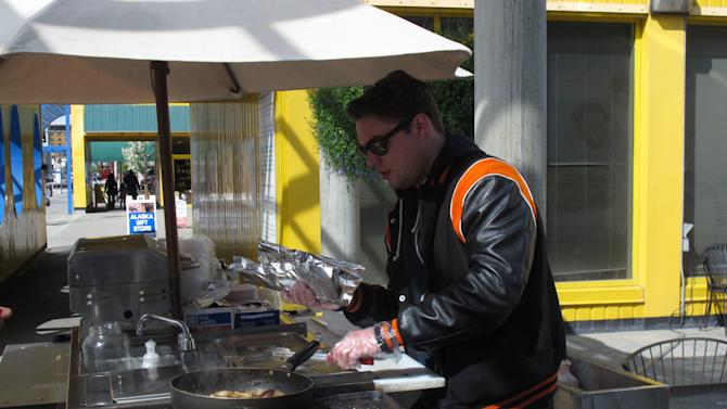 """In this photo taken Thursday, May 31, 2012, in Anchorage, Scott Root of Anchorage tends to a customer at a downtown hot dog stand. Travel and Leisure poll readers have named Anchorage residents as the nation's worst-dressed. New York came in tops in the poll. Root says when you go to New York, you want to dress to impress at the fancy hotspots. But in Anchorage, Root said you dress differently because """"it's all outdoors."""" (AP Photo/Mark Thiessen)"""
