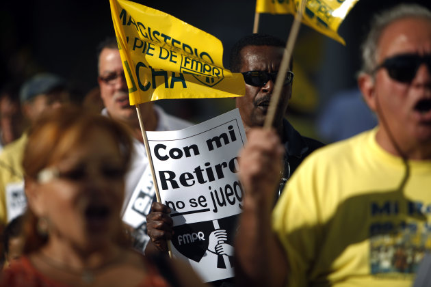 "A retiree carries a sign that reads in Spanish ""Do not play with my pension"" during a protest outside the government pension headquarters in San Juan, Puerto Rico, Wednesday, Jan. 30, 2013. Puerto Rico is confronting what economists and financial analysts say is a ticking fiscal time bomb: A public pension system with a $37.3 billion unfunded liability that must be addressed soon, at a time when the U.S. island territory's government has little money to spare, or thousands of retirees could start to see benefit cuts. (AP Photo/Ricardo Arduengo)"