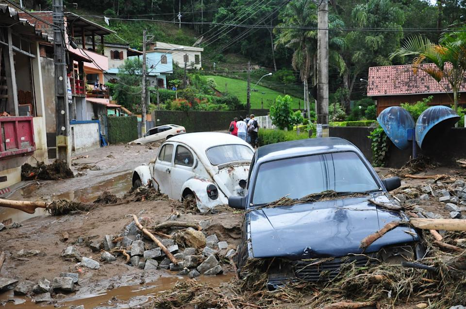 Cars sit in debris in a flooded street in Teresopolis, Rio de Janeiro state, Brazil, Wednesday Jan. 12, 2011.  Torrential summer rains tore through Rio de Janeiro state's mountains, killing at least 140 people in 24 hours, Brazilian officials said Wednesday.  (AP Photo/Roberto Ferreira, Agencia O Dia)