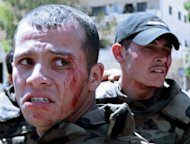 Wounded Syrian soldiers react following a roadside bomb attack which targeted their convoy as they escorted UN observers in the restive southern city of Daraa. A roadside bomb wounded six soldiers as they escorted a convoy of UN peace observers, including the general who heads the mission, in southern Syria on Wednesday, an AFP photographer said