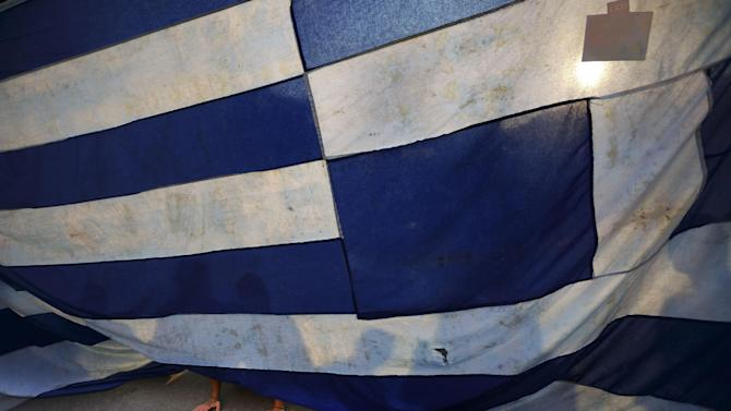 A supporter of the NO vote in the upcoming referendum kneels paying his respects in front of a representation of the Greek flag during a rally at Syntagma square in Athens on Monday, June 29, 2015. Anxious Greek pensioners swarmed closed bank branches and long lines snaked outside ATMs as Greeks endured the first day of serious controls on their daily economic lives ahead of a July 5 referendum that could determine whether the country has to ditch the euro currency and return to the drachma. (AP Photo/Daniel Ochoa de Olza)