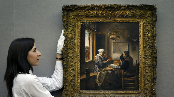 A Sotheby's employee adjusts a painting by Dutch artist Jan Havickszoon Steen called 'The Prayer Before the Meal' during a press viewing in London, Friday, Nov. 30, 2012. The painting estimated at 5-7 million pounds (8-11 million US Dollars) will go on sale in the evening sale of Old Master Paintings and Drawings on Dec. 5 in London. (AP Photo/Kirsty Wigglesworth)