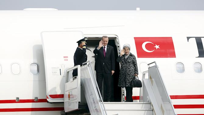 Turkey's President Recep Tayyip Erdogan and his wife Emine wave as they depart from Halim Air Base after finishing his three-day visit to Indonesia, in Jakarta