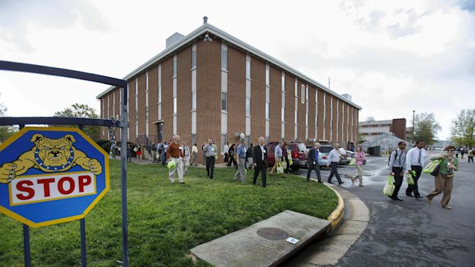 Students and faculty evacuate the North Carolina A&T State University campus at Drew Drive after a person reported seeing a man possibly with a rifle on the campus, Friday, April 12, 2013, in Greensboro, N.C. The university updated its website Friday morning to advise that students should stay inside and lock their doors and windows. (AP Photo/News & Record, Jerry Wolford)