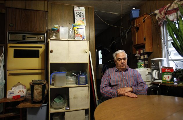 In this Sept. 15, 2011 photo, Bill Ricker, 74, sits at the kitchen table of his trailer home, in Hartford, Maine. Ricker, who has two college degrees, was injured in the late 1980s and hasn't worked s