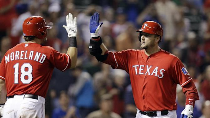 Texas Rangers' A.J. Pierzynski, right, high-fives Mitch Moreland (18) after hitting a solo home run in the fourth inning of a baseball game against the Tampa Bay Rays, Monday, April 8, 2013, in Arlington, Texas. (AP Photo/LM Otero)