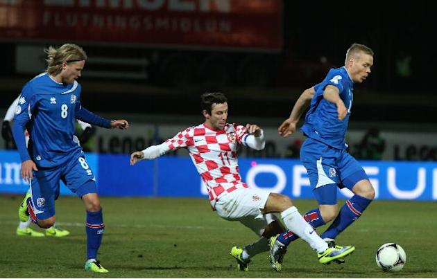 Iceland's Kolbeinn Sigthorsson, right, is challenged for the ball by Croatia's Darijo Srna as Iceland's Birkir Bjarnason, left, looks on during their World Cup qualifying playoff first leg soccer matc