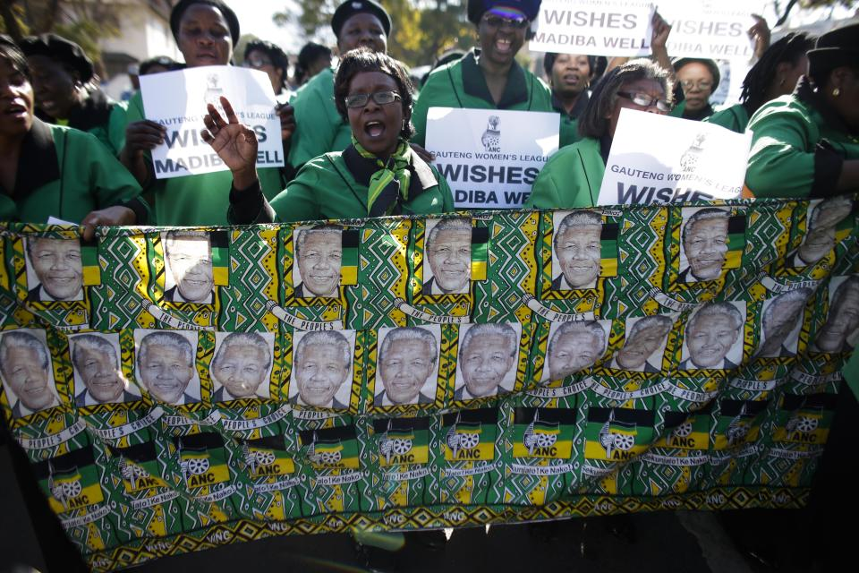 Women of the ANC women league sing and hold posters in support of former South African President Nelson Mandela at the entrance of the Mediclinic Heart Hospital where Nelson Mandela is being treated in Pretoria, South Africa, Thursday, July 4, 2013. (AP Photo/Markus Schreiber)