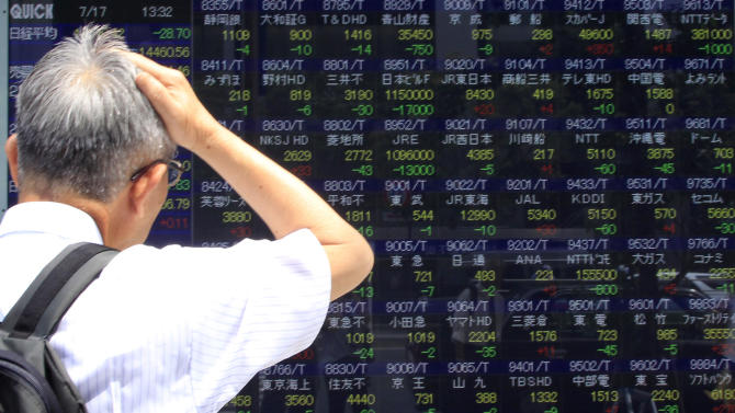 A man watches an electronic stock indicator in Tokyo, Japan, Wednesday, July 17, 2013. Asian stock markets were mixed Wednesday as investors remained cautious ahead of testimony from U.S. Federal Reserve Chairman Ben Bernanke. (AP Photo/Azusa Uchikura)