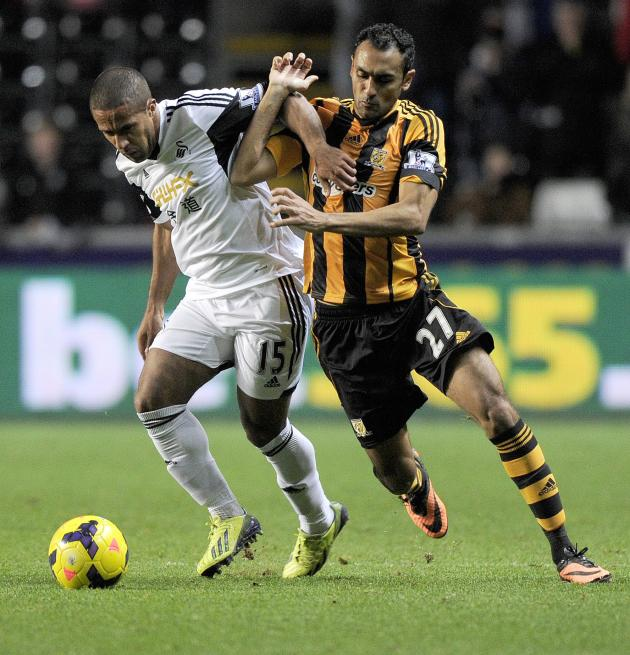 Swansea City's Wayne Routledge challenges Hull City's Ahmed Elmohamady during their English Premier League soccer match at the Liberty Stadium in Swansea