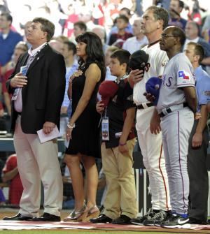 From left, John Green stands next to his wife Roxanna and their son Dallas along with American League manager Ron Washington of the Texas Rangers and National League manager Bruce Bochy of the San Francisco Giants during the playing of the national anthem the MLB All-Star baseball game Tuesday, July 12, 2011, in Phoenix. (AP Photo/Mark J. Terrill)