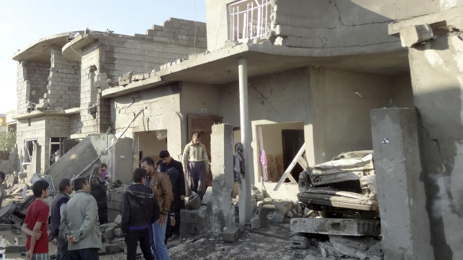 People inspect the scene of a car bomb attack in Kirkuk, 180 miles (290 kilometers) north of Baghdad, Iraq, Wednesday, Nov. 14, 2012. Iraqi insurgents unleashed a new wave of bombings across the country early Wednesday targeting security forces and civilians, killing and wounding scores of people, police said. (AP Photo/Emad Matti)