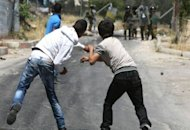Palestinian youths throw stones at Israeli soldiers outside the al-Aroub Palestinian refugee camp near the West Bank city of Hebron. According to Defence for Children International, around 700 West Bank children are arrested every year, most accused of stoning Israeli soldiers and military vehicles