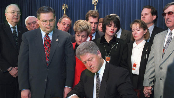 FILE - In this Tuesday, March 12, 1996 file photograph, members of Congress and family members of those killed by Cuban jet fighter pilots look on, as President Clinton signs Helms-Burton bill in the Old Executive Office Building in Washington. From left are, Sen. Jesse Helms, R-N.C., co-author of the bill; Sen. Frank Lautenberg, D-N.J.; Rep. Robert Menendez, D-N.J.; and Rep. Leana Ros-Lehtinen, R-Fla. Others are unidentified. U.S. Sen. Robert Menendez, whose political career began in a place with a reputation as one of the most corrupt corners of the nation, has often found himself the focus of ethics allegations as he has risen to prominence. (AP Photo/Denis Paquin, file)