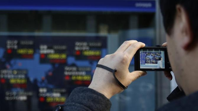 Pedestrian takes pictures of an electronic board displaying share index prices outside a brokerage in Tokyo