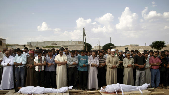 Relatives and mourners of Abdullah Alrayzar, 23, left, and Mohammed Abdul Samee, 35, pray during a funeral for four men, who were killed in a government airstrike in Marea, on the outskirts of Aleppo, Syria, Tuesday, Sept. 11, 2012. (AP Photo/Muhammed Muheisen)