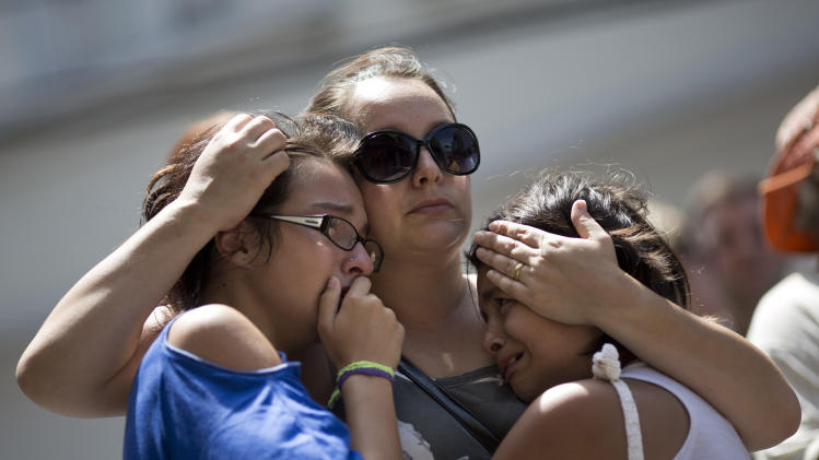 Girls cry in front of a makeshift memorial outside the Kiss nightclub where a fire killed over 230 people in Santa Maria, Brazil, Tuesday, Jan. 29, 2013. The repercussions of a tragic nightclub fire in southern Brazil widened Tuesday as mayors around the country cracked down on such venues in their own cities and investigators searched two other nightspots owned by a partner in the club that caught ablaze. Most of the dead were college students 18 to 21 years old, but they also included some minors.  (AP Photo/Felipe Dana)