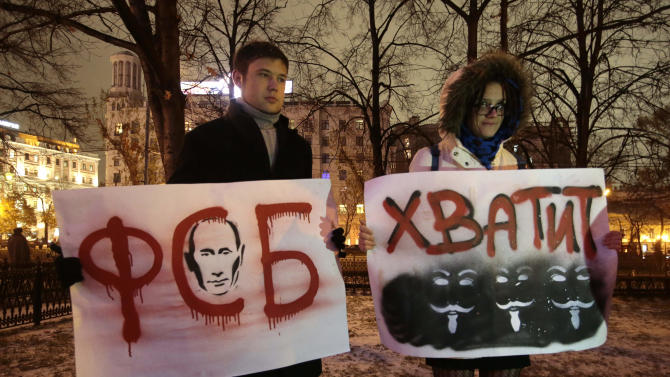 """Demonstrators hold posters featuring Russian President Vladiimir Putin and reading """"FSB, You Stop It,"""" during a protest rally  in Moscow, Russia, Tuesday, Oct. 30, 2012.  FSB is a Russian acronym for the Federal Security Services. Several hundred people rallied in central Moscow Tuesday in support of jailed opposition activists. The rally, which was sanctioned by authorities, went on peacefully amid heavy police cordons, and attracted supporters of both leftist and liberal parties, who urged the government to release more than a dozen of people facing accusations over their involvement in an opposition protest in May that ended in clashes with police. (AP Photo/Mikhail Metzel)"""