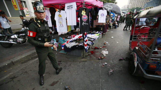 A military police officer stands at the scene of an explosion at a main protest site in Bangkok, Thailand, Sunday, Feb. 23, 2014. More than a dozen people were hurt Sunday by a small explosion at an anti-government protest in Bangkok, less than a day after a bloodier attack in an eastern province killed one child and left about three dozen people wounded. (AP Photo/Wally Santana)